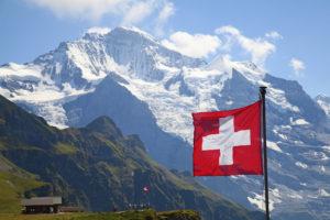 Государственный флаг Швейцарии на фоне Альп